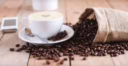 Taza de café humeante junto a granos de café.